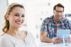 Smiling creative businesswoman with her colleague behind Royalty Free Stock Photo