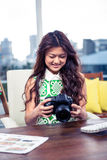Smiling creative businesswoman holding camera Royalty Free Stock Photo
