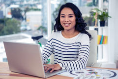 Smiling creative businesswoman using laptop Stock Images