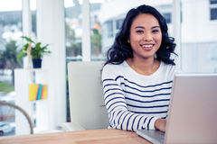 Smiling creative businesswoman using laptop Stock Image