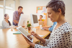 Smiling creative businesswoman using a tablet Royalty Free Stock Photos
