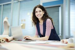 Smiling creative designer using laptop in tailoring studio royalty free stock photos