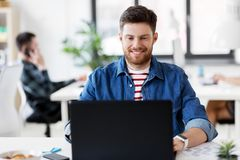 Smiling creative man with laptop working at office Royalty Free Stock Photography