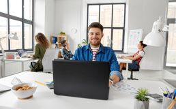 Smiling creative man with laptop working at office royalty free stock images