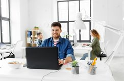 Smiling creative man with laptop working at office Royalty Free Stock Image