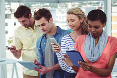 Smiling creative team standing in a line using technology Stock Images