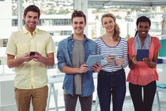 Smiling creative team standing in a line using technology Stock Photo
