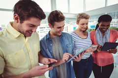 Smiling creative team standing in a line using technology Royalty Free Stock Images