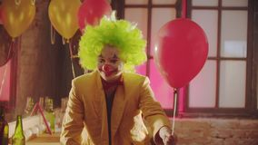 A smiling creepy clown in the colorful costume hands the ball to the viewer and smile
