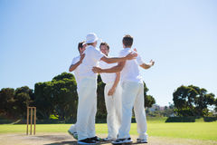 Smiling cricket players standing at field. Against clear sky royalty free stock image