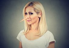 Smiling cunning woman with long nose. Liar concept. Face expressions, emotions, feelings Royalty Free Stock Images