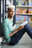 Smiling curious student in university library. Smiling curious hipster black college student with tattoos on arm sitting on floor in library and reading book, he royalty free stock image