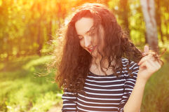 Smiling curly brunette outdoors backlit by sun. With flares. Close up young woman portrait outdoor. Happy summertime mood Royalty Free Stock Photography