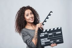Female holding movie clapper board. Smiling curly female holding movie clapper board, slate film Stock Photos