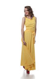Smiling curly girl posing in stylish yellow dress Royalty Free Stock Images