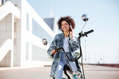 Smiling curly girl sitting on modern motorbike outdoors Imagen de archivo