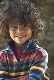Smiling, curly haired boy in colorful sweater Stock Photography