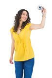 Smiling curly haired brunette taking picture of herself Royalty Free Stock Images