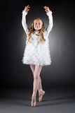 Smiling curly-haired girl dancing on pointes. In studio Stock Image