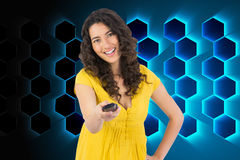 Smiling curly haired pretty woman changing channel with remote Royalty Free Stock Image