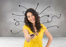 Smiling curly haired pretty woman changing channel with remote Royalty Free Stock Images
