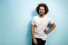 Smiling curly-headed man in white T-shirt with a hand on the hip. An easy going person with positive outlook. Happiness royalty free stock photos