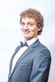 Smiling curly man in black and bow tie Stock Photography