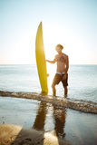 Smiling curly man holding his surf board at the beach. Smiling young curly man holding his surf board while standing in the ocean at the beach Royalty Free Stock Photo