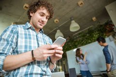 Smiling curly man using cellphone while his friends studying. Smiling young curly men in plaid shirt using cellphone while his friends studying and making Royalty Free Stock Image