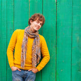 Smiling curly man in yellow sweater and scarf on green wooden ba Royalty Free Stock Photo