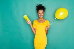Happy mulatto girl drinking coffe at studio background. Smiling curly mulatto girl in bright yellow dress with take away coffee cup and balloon. Young cheerful Stock Photography