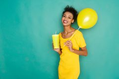 Happy mulatto girl drinking coffe at studio background. Smiling curly mulatto girl in bright yellow dress with take away coffee cup and balloon. Young cheerful Stock Image