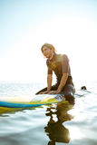 Smiling curly surfer man in swimwear sitting on surf board Stock Photos
