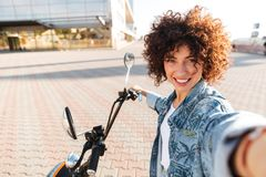 Smiling curly woman sitting on modern motorbike outdoors Stock Photos