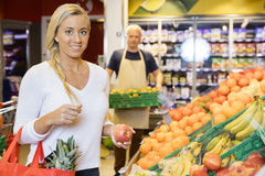 Smiling Customer Holding Apple In Supermarket Stock Image