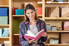 Smiling Customer Holding Notebook While Sitting Royalty Free Stock Photography