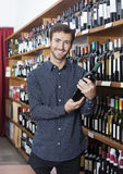 Smiling Customer Holding Wine Bottle In Store. Portrait of smiling young male customer holding wine bottle in store Royalty Free Stock Photography