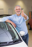 Smiling customer leaning on car while giving thumbs up Stock Photo