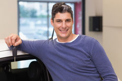 Smiling customer leaning on car while holding his key Royalty Free Stock Photo