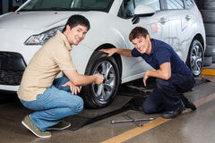 Smiling Customer With Mechanic Repairing Car Royalty Free Stock Photography