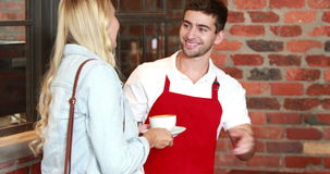 Smiling customer paying by credit card stock footage
