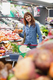 Smiling customer picking onions Royalty Free Stock Images