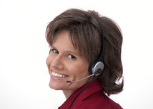 Smiling customer service. Closeup of beautiful female customer representative with headset smiling against white background royalty free stock photos