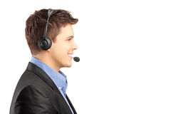 Smiling customer service employee in profile with headset on. Isolated on white background royalty free stock photography