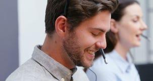 Smiling customer service executives talking on headset at desk 4k