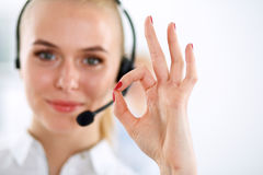 Smiling customer service girl showing ok, isolated Royalty Free Stock Images