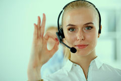 Smiling customer service girl showing ok, isolated Stock Image