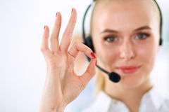 Smiling customer service girl showing ok, isolated Royalty Free Stock Image