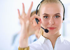 Smiling customer service girl showing ok, isolated Stock Images