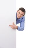 Smiling customer service male operator pointing to blank white billboard. Royalty Free Stock Images